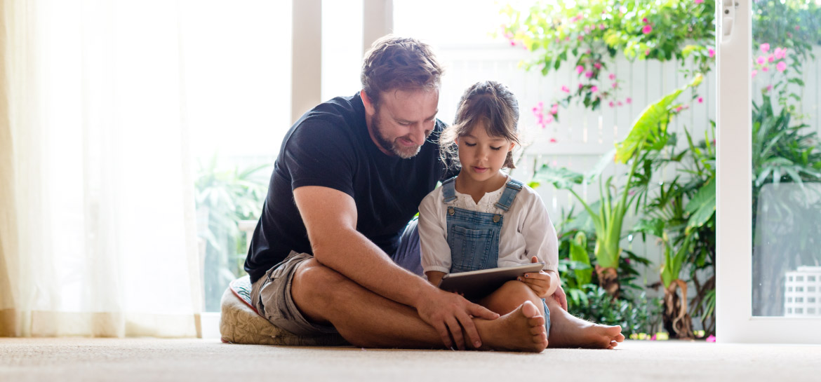 A man and his daughter looking at a tablet together