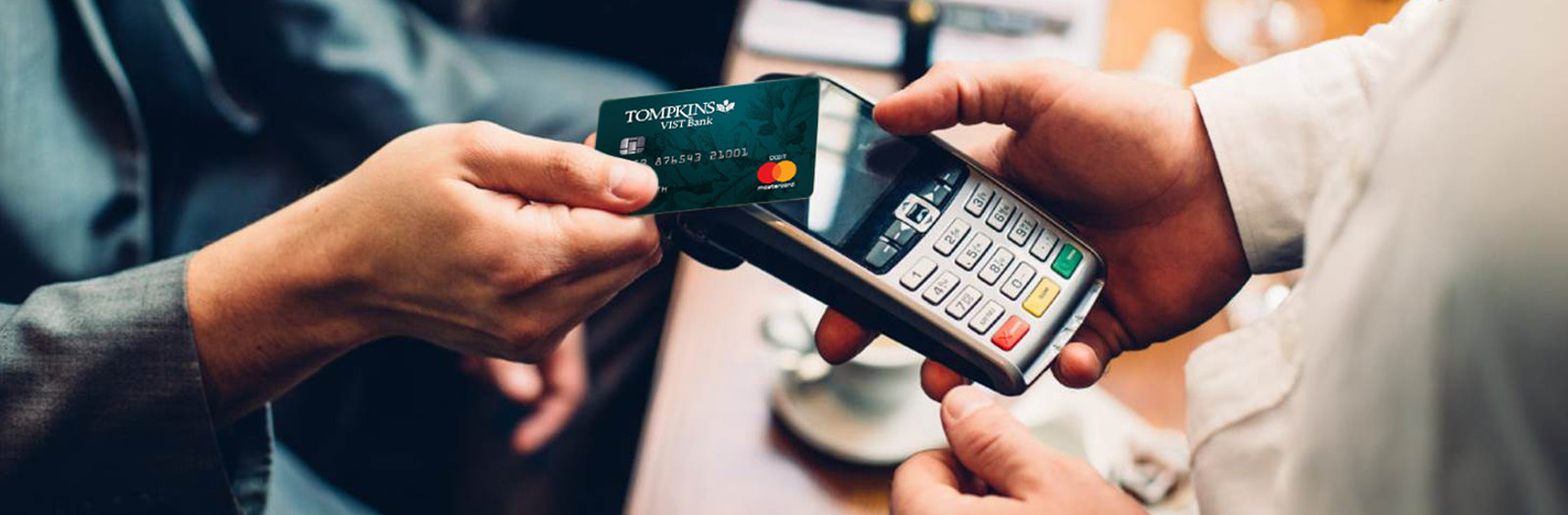 Tompkins VIST Bank debit mastercard in hand making purchase